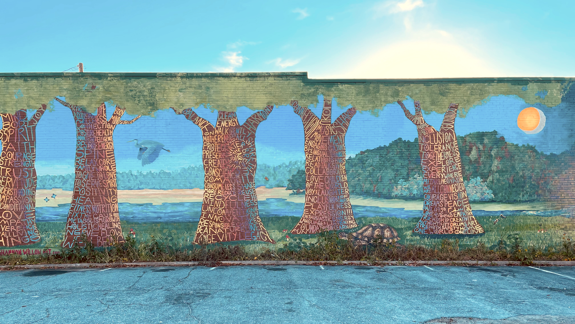 Clarkston mural of trees with words written on them and a pond backdrop on a sunny day.